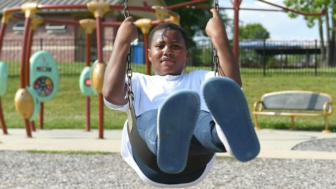 Desmond Fenderson of East Canton pumps his legs to pick up speed on the swing at the Boettler Park playground in Green.The site was bustling with kids Wednesday afternoon, the first day playgrounds have been open since the COVID-19 shutdown.