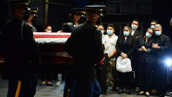 Ailina Fernandes, second from right, the mother of Sgt. Elder Fernandes, watches as her son's casket is carried into the Russell & Pica Funeral Home on Belmont Street in Brockton, Tuesday, Sept. 1, 2020. Elder Fernandes' body was returned to Massachusetts via a flight into Boston Logan International Airport. Fernandes was met at the airport by family members and then given a police escort to his hometown of Brockton, where he will be buried.