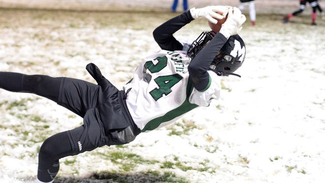Marshifield's Jacob Brawn makes a catch in the snow Friday night against Bridgewater in Div. 1 Midgets youth football 7-on-7 action.