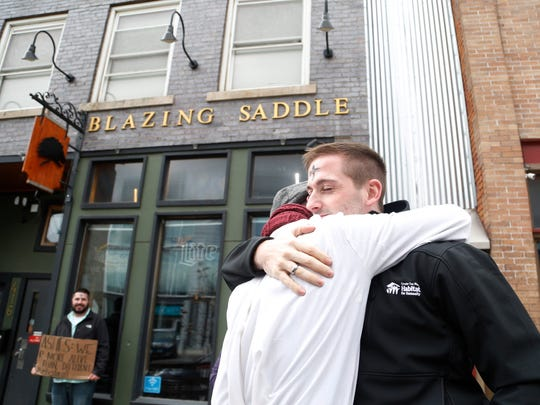 The Rev. Sam Fisher, pastor at First United Methodist Church in Indianola, gives Christopher Civitate of Des Moines a hug Wednesday, March 1, 2017 after marking his forehead with glitter ashes outside of Blazing Saddle in the East Village in Des Moines for Ash Wednesday.