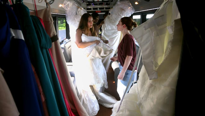 Kylie Lambert (L) gets some help from her cousin Chelsea Miner as she picks out a wedding dress from a limousine coach bus outside Alfred Angelo Bridal in Greece.  Stella's Bridal Boutique stepped up to offer free dresses to brides who had ordered from Alfred Angelo Bridal, which abruptly closed.