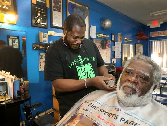 Master barber Eric Turner, left, trims up James E.