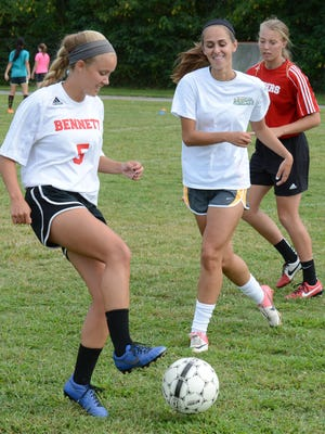 James M. Bennett High School Senior Allie O'Leary, left, works on a 2 on 1 drill with Junior Abbey Hobbs, center, and Junior Brittany Boardman during practice Wednesday at the school.