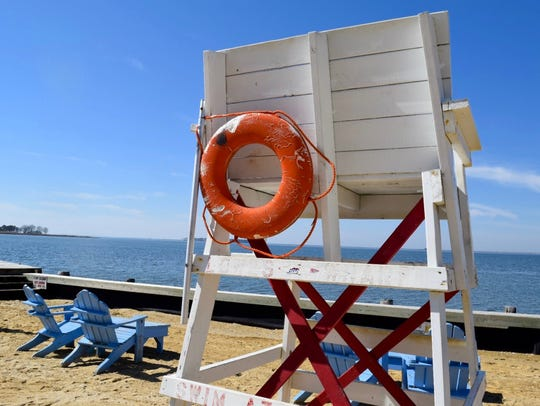 A hand-crafted lifeguard chair sits on the sand of