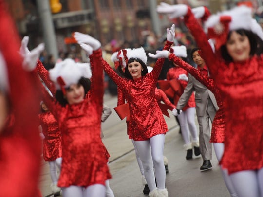 Marchers in sparkly red dresses and Santa hats make their way down Woodward during the Thanksgiving Day Parade in Detroit on Thursday, Nov. 24, 2016.