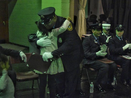 Sherman Trotman, who was promoted to lieutenant, hugs his daughter during Friday's promotion ceremony.
