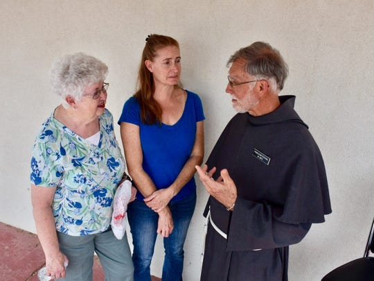 Father Tom Smith, director of the Holy Cross Retreat House, is seen greeting visitors Theresa Daviet, center and her mother, Marilyn Kerschen, left.