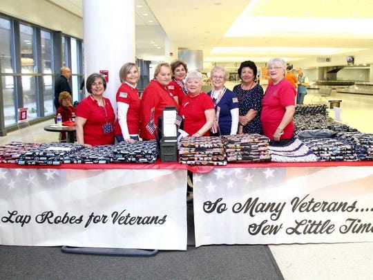Members of Lap Robes for Veterans handing out their handmade lap robes to veterans at a recent Honor Flight arrival at the Greater Rochester International Airport. Lap Robes for Veterans is one of two non-profits that will receive the proceeds from the upcoming Pork for Patriots event at McCracken Farms in Sweden.