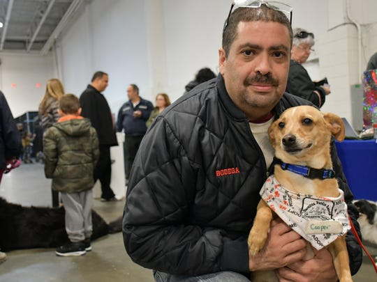 Luis Bodega with Cooper, the Labrador retriever-Chihuahua mix he adopted at the Super Adoption event Sunday at the Meadowlands Exposition Center.