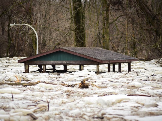 The roof of a pavilion at Croswell's Riverbend Park can be seen above the flooded Black River Wednesday.