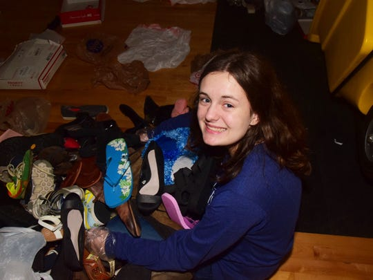 Kara McNutt, 16, is earning service hours processing a mountain of shoes.