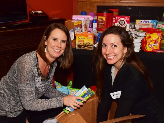 Dr. Jennifer Scoles and chiropractic assistant Faith Julian pack a box for shipment to service personnel overseas at the Scoles Chiropractic office at 7555 Oak Ridge Hwy.