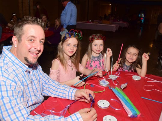 Ryan Wells helps make crowns with daughter Janie Wells,