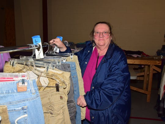 Volunteer Elizabeth Broglin organizes a clothing rack.