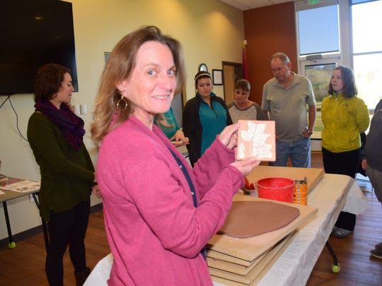 Natalie Landrey shows an example of a sgraffito tile where the image is scratched into the clay.