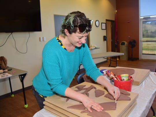 Artist Jillian Hirsch carves out a clay leaf during the second of three workshops to create a mosaic mural at Karns Senior Center Thursday, March 22.