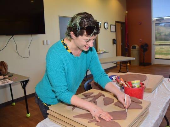 Artist Jillian Hirsch carves out a clay leaf during