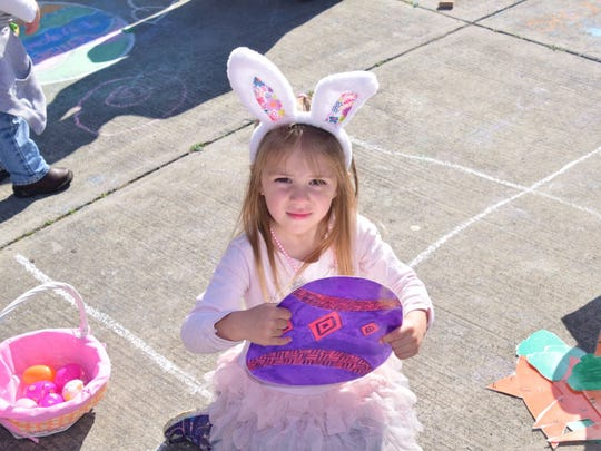 Caroline Dabbs, 3, gets into the Easter spirit with bunny ears and a giant Easter Egg.