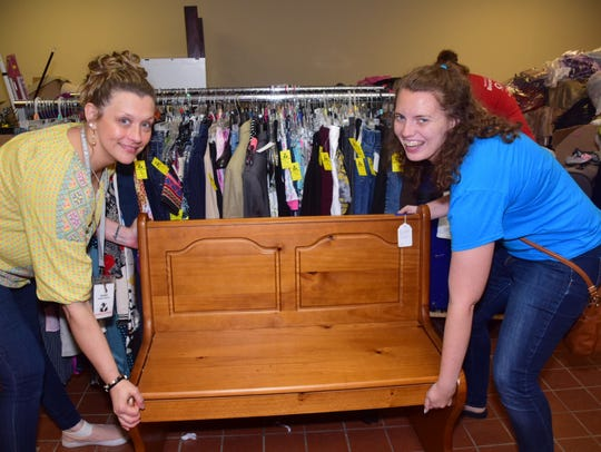 Amber Auston and Lisa Howard move a handmade bench