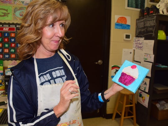 Art teacher Teresa McNelly with a student's 3-D painting
