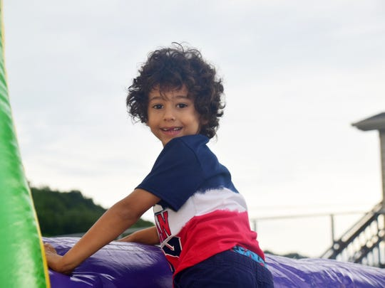 """Gabriel Ball, 5, in his """"All American Boy"""" T-shirt flashes a gap-toothed grin as he climbs an inflatable slide."""