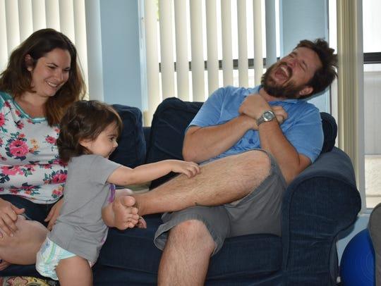 Skye Savren-McCormick tickles her father, Todd Savren-McCormick,