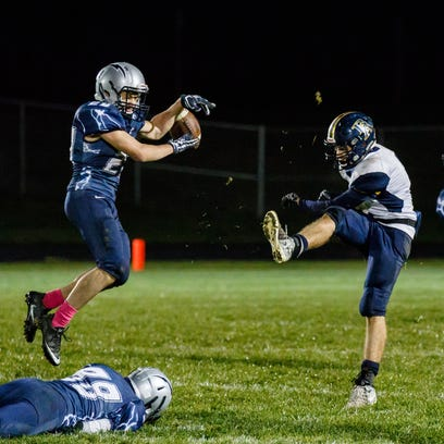 Lake Country Lutheran junior Michael Schumacher (left) blocks a punt by Brookfield Academy's Mason Dieck (7) during the game in Hartland on Thursday, Oct. 13, 2016.