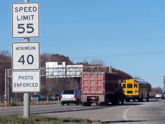 FILE - In this Nov. 12, 2013, file photo, vehicles pass a highway sign along Interstate 380 in Cedar Rapids, Iowa, warning drivers that the 55-mph speed limit is enforced by speed cameras.