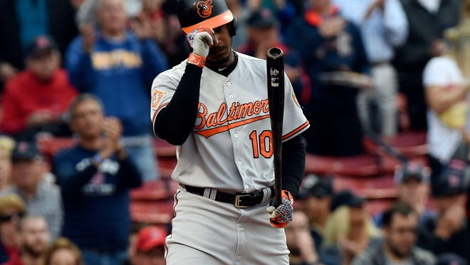 Baltimore Orioles center fielder Adam Jones tips his helmet in reaction to a standing ovation he received Tuesday night prior to his first inning at-bat against the Boston Red Sox at Fenway Park.