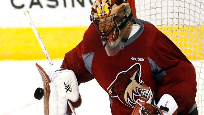 Arizona Coyotes goalie Mike Smith blocks a shot during  training camp at Gila River Arena in Glendale on Saturday, Sept. 19, 2015.