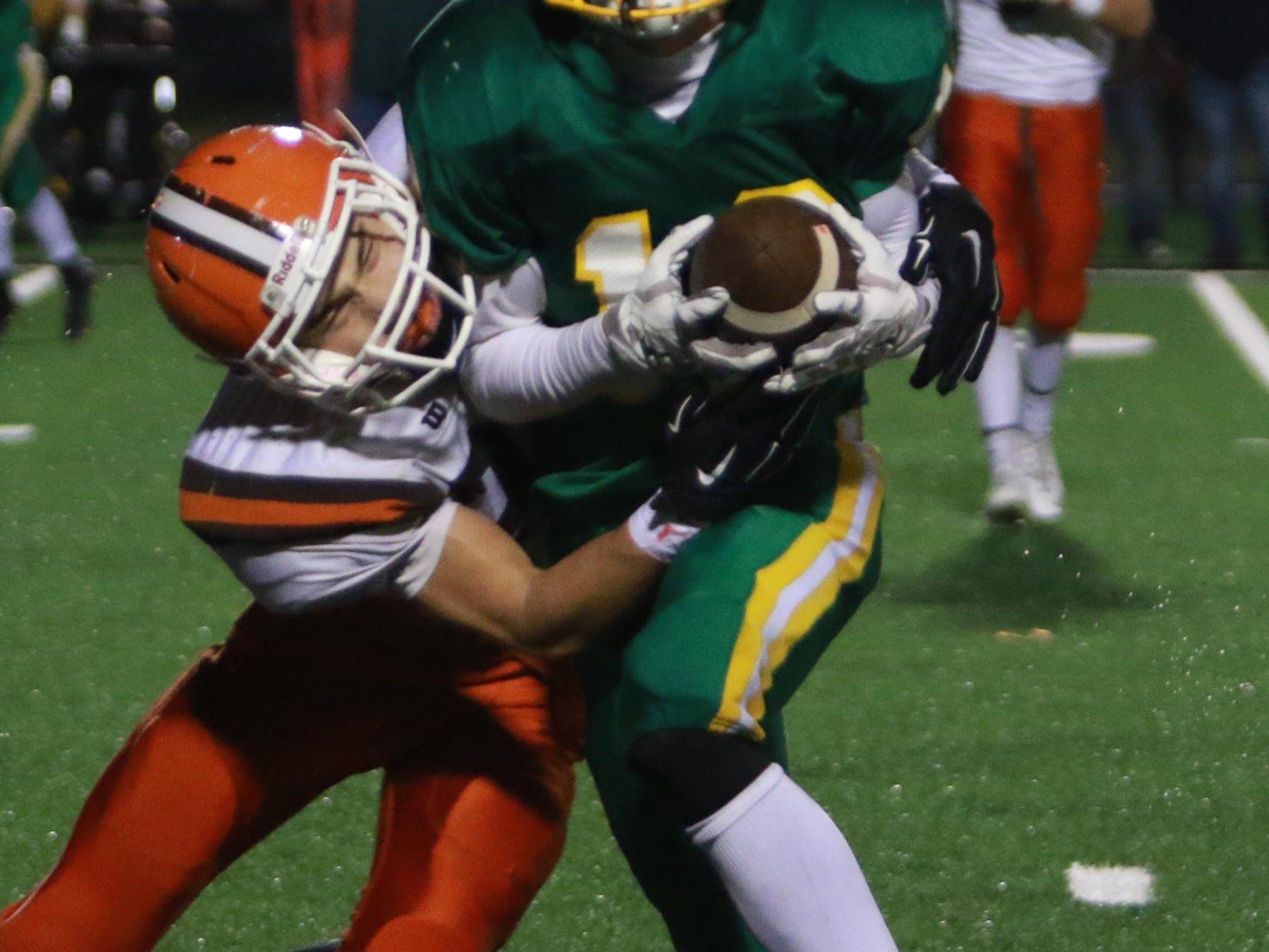 Heath senior linebacker Avery Hogue wraps up Newark Catholic's Jack Wollenburg on Saturday at White Field.