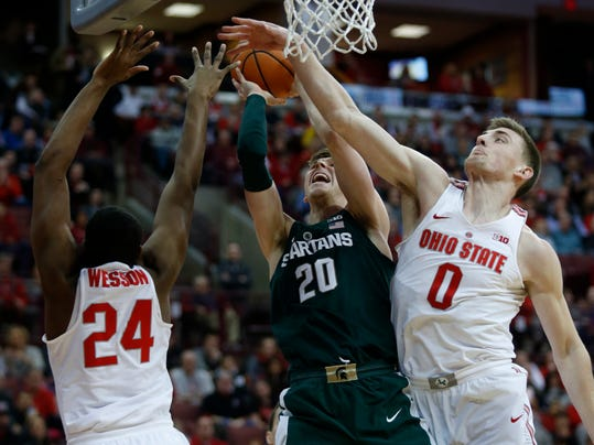 Michigan State guard Matt McQuaid, center, goes up to shoot between Ohio State forward Andre Wesson, left, and center Micah Potter during the first half of an NCAA college basketball game in Columbus, Ohio, Sunday, Jan. 7, 2018. (AP Photo/Paul Vernon)