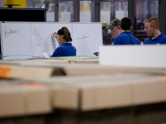 Procter and Gamble employees train on a line to produce