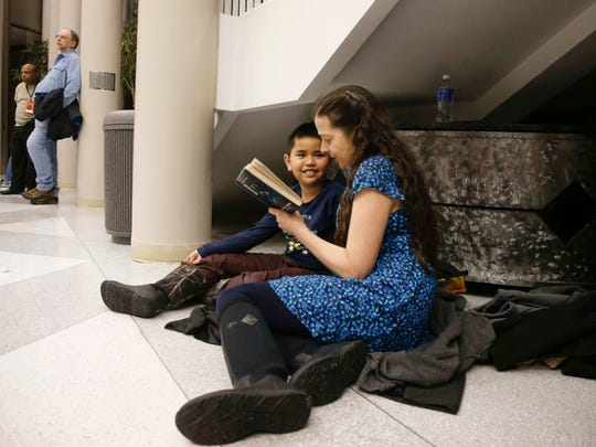 Barb Schilf of Cedar Falls reads a book to her son, Owen Dribbler, 10, while they wait to hear from Sen. Hillary Clinton at the Gallagher Bluedorn Performing Arts Center in Cedar Falls at 7:09 p.m. Tuesday, Jan. 16, 2016. The Democratic presidential candidate arrived late due to road conditions in northeast Iowa, where she spoke earlier.