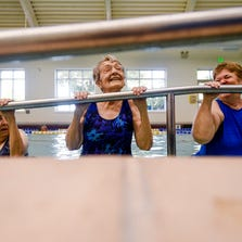 Maxine Bell, 100, does a chin-up at the end of a water aerobics class at the Senior Center, Wednesday, July 10, 2014. Bell, who has been attending the Senior Center since its opening in 1995, said she chose all new classes to try this year.