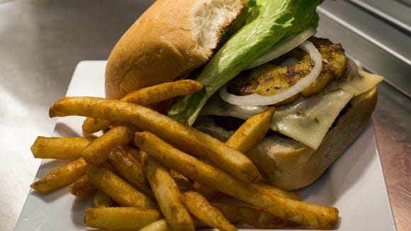 A custom-ordered Spicy Broaddus Burger is prepared with onions, lettuce, pepperjack cheese, and a grilled slice of pineapple at Broaddus Burgers in Lafayette, La., Tuesday, November 25, 2014.