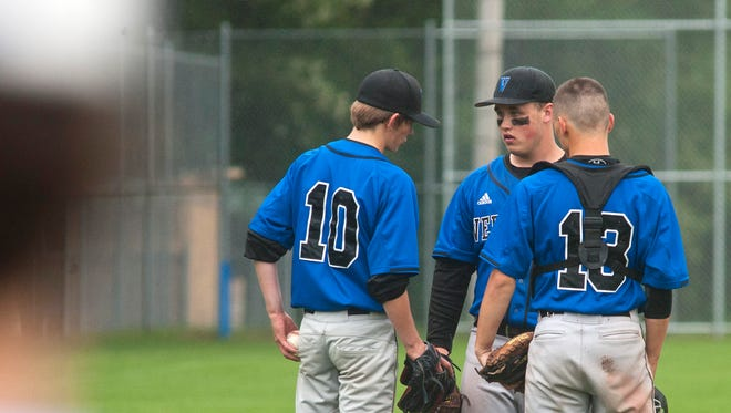 Vergennes pitcher Hunter O'Connor, left, confers with teammates at the mound during Tuesday's playoff game against Milton.