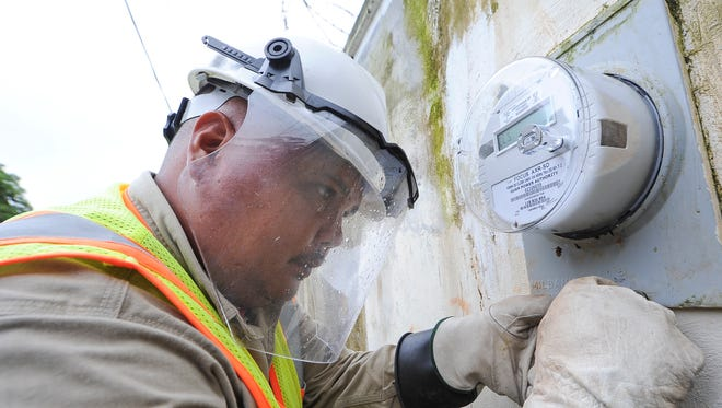 Apex CoVantage installer Derek Cruz places a locking seal on a meter box after installing a new smart meter at a Yigo residence in 2012.
