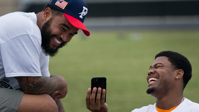 Derek Barnett, a Nashville native and defensive end for the Super Bowl champion Philadelphia Eagles, laughs with Tennessee defensive back Todd Kelly Jr. during Barnett's football camp Saturday at Overton High School.