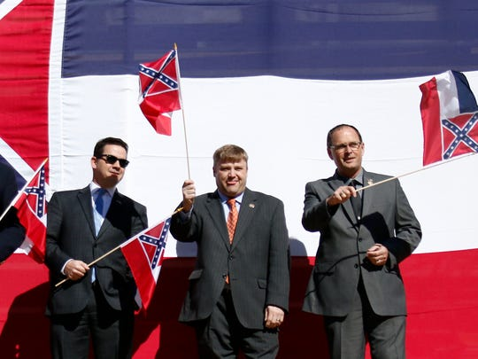 In this Jan. 16, 2016, file photo, a group of Mississippi flag supporting lawmakers, from left, Republican Reps. Robert Foster of Hernando, Dana Criswell of Olive Branch, Ken Morgan of Morgantown, Chris Brown of Nettleton, Bubba Carpenter of Burnsville and William Shirley of Quitman, pose in front of a large Mississippi state flag on the south steps of the Capitol in Jackson, Miss., during a rally sponsored by the Sons of Confederate Veterans and other groups in support of keeping the Confederate battle emblem on the state flag. Shirley wrote and presented a flag amendment attached to a universities finance bill that would withhold proposed tax exemptions to public universities that refuse to fly the state flag.