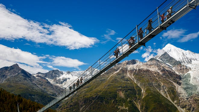 People walk on the 'Europabruecke' bridge, the world's longest pedestrian suspension bridge with a length of 494meters, after the official inauguration of the construction in Randa, Switzerland on July 29, 2017. The bridge is situated on the Europaweg that connects the villages of Zermatt and Graechen.