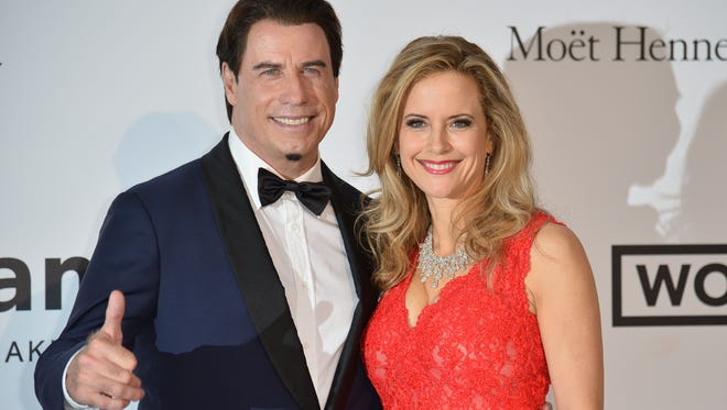 John Travolta (L) and his wife actress Kelly Preston pose as they arrive for the amfAR 21st Annual Cinema Against AIDS during the 67th Cannes Film Festival at Hotel du Cap-Eden-Roc in Cap d'Antibes, southern France, on May 22, 2014.