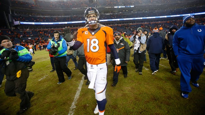 Broncos quarterback Peyton Manning (18) walks off the field after his loss to the Indianapolis Colts in the 2014 AFC Divisional playoff football game at Sports Authority Field at Mile High. The Colts won 24-13.
