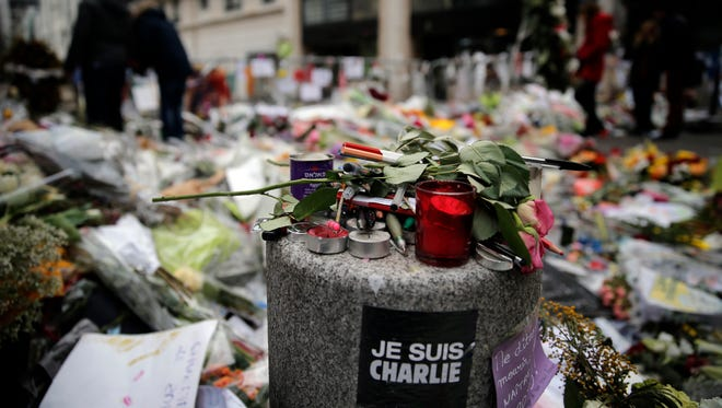 "Pencils, candles and flowers are set up next to the ""Charlie Hebdo"" newspaper office in Paris on Jan. 21."