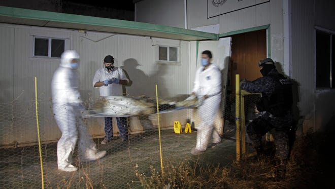 Forensic workers remove a body found at the crematorium of an abandoned funeral home near Acapulco, Mexico, on Feb. 6, 2015.
