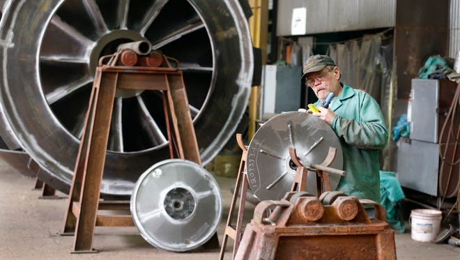 A man works on parts to builds fans for industrial ventilation systems at the Robinson Fans plant in Harmony, Pa.