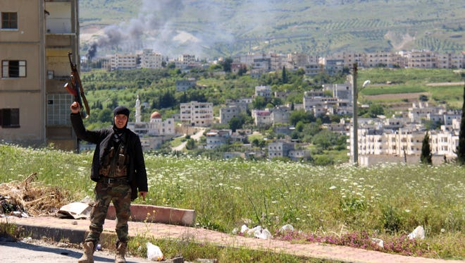 A rebel fighter raises his weapon, as smoke billows in the background, in the northern Syrian town of Jisr al-Shughur on Saturday.