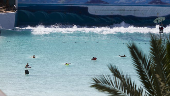 The giant wave from the Waikiki Beach Wave Pool comes roaring out of the back of the pool at Big Surf, Sunday, May 17, 2015, in Tempe, Ariz.