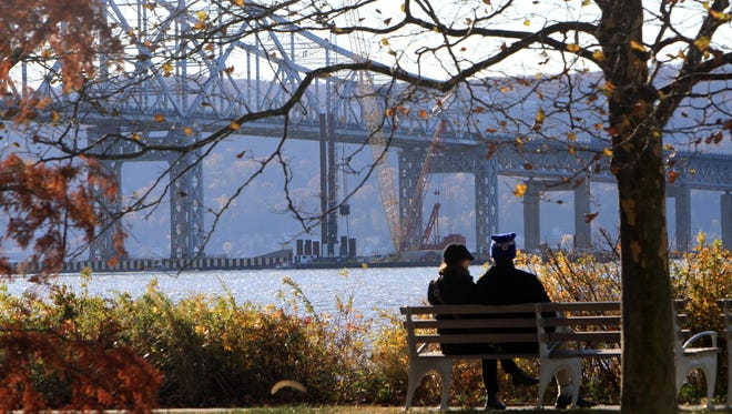 A couple sits on a bench along the Hudson River in Tarrytown as bridge construction is under way for the new Tappan Zee Bridge Nov. 13,  2013. ( Frank Becerra Jr / The Journal News )