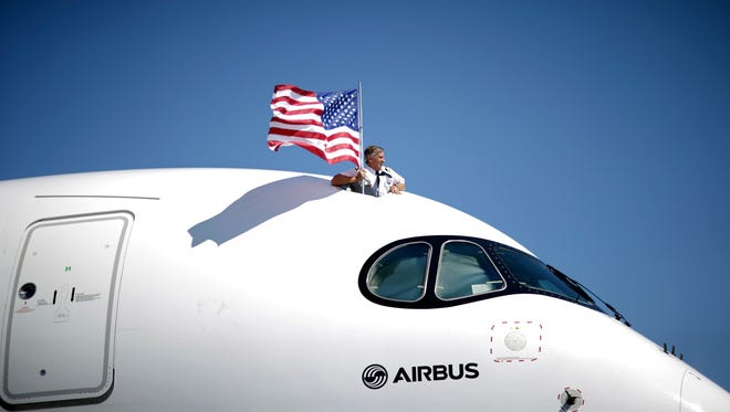 Airbus test flight engineer Bruno Bigand holds a flag as he stands in the cockpit hatch of a Airbus A350 XWB test flight aircraft at Newark Liberty International Airport on July 16, 2015.